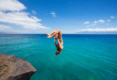 Woman doing backflip off cliff into the ocean. Summer fun lifestyle.