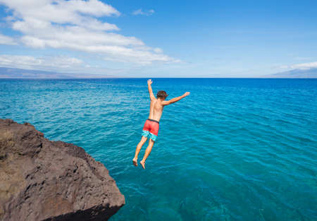 cliff jumping: Man jumping off cliff into the ocean. Summer fun lifestyle. Stock Photo