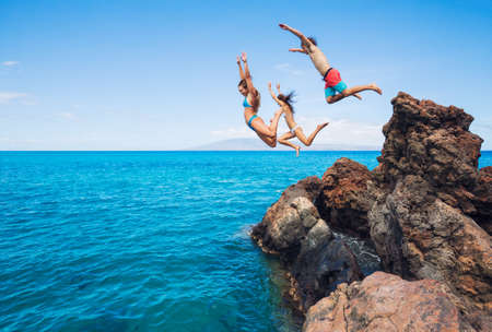 adventure sports: Summer fun, Friends cliff jumping into the ocean.