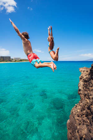 extreme danger: Summer fun, Friends cliff jumping into the ocean.