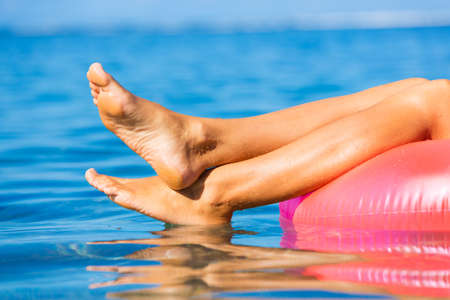 pies sexis: Hermosa chica sexy flotando en balsa en el océano tropical. Cierre de vista de los pies. Concepto de relajación. Foto de archivo