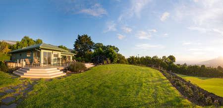 庭園と緑の草が茂った芝生と郊外の家