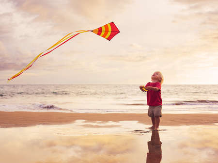 Happy young boy flying kite on the beach at sunset photo