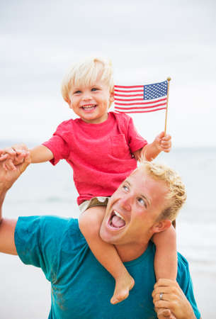 Father and son playing on the beach with American flag. USA celebrate 4th of July. photo