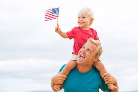 Father and son playing on the beach with American flag. USA celebrate 4th of July.