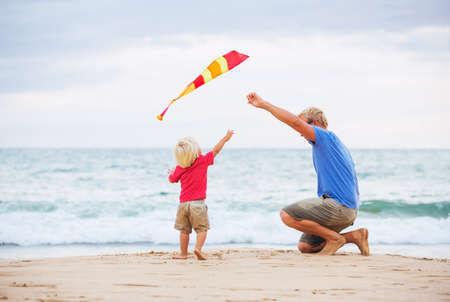 Happy father and son playing with kite at the beach at sunset photo