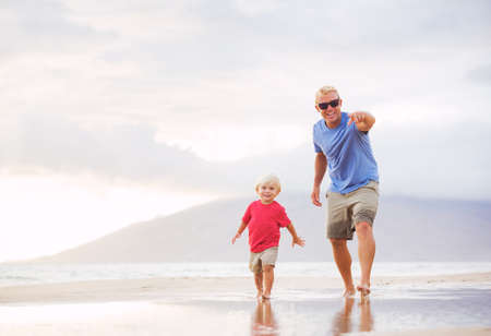 Happy father and son walking on the beach at sunset Reklamní fotografie