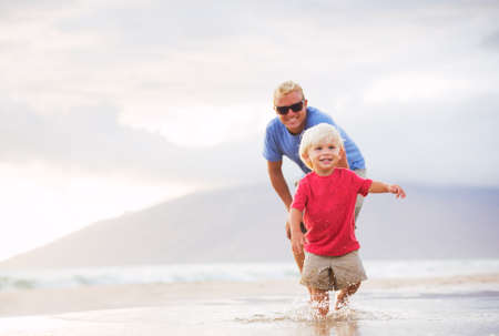 family time: Happy father and son walking on the beach at sunset Stock Photo