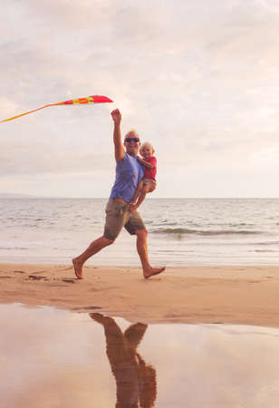 Father and son running with kite at the beach at sunset photo