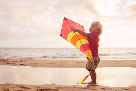 Happy young boy playing with kite on the beach at sunset photo