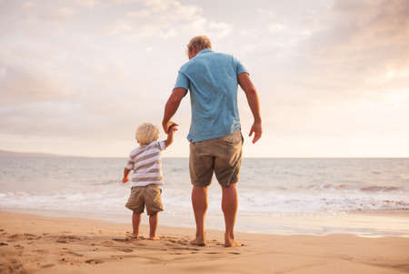 cute guy: Father and son holding hands walking on the beach at sunset
