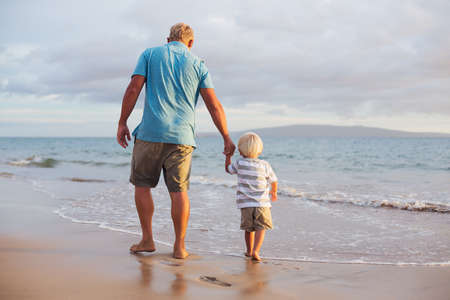 Happy father and son walking on the beach at sunset Stock Photo