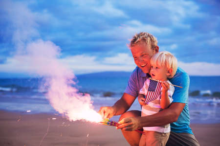 Father and son lighting sparklers on the beach at sunset photo