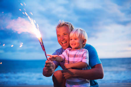 Father and son lighting sparklers on the beach at sunset Standard-Bild