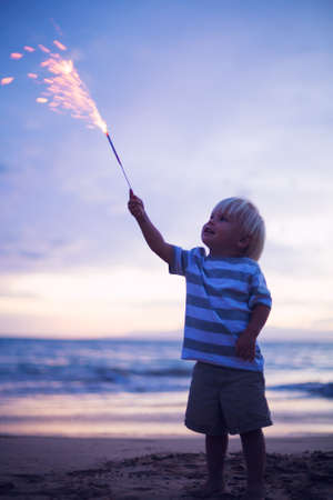 Young boy lighting sparkler on the beach at sunset