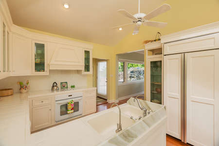 down lights: Classic kitchen in beautiful bright home with wood floors Stock Photo
