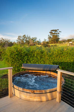 Beautiful wooden hot tub jacuzzi outdoors on deck Stock Photo