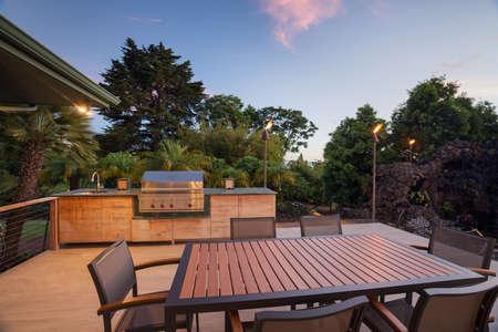 裏庭のパティオ デッキのダイニング テーブルとバーベキュー グリル