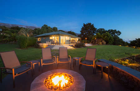 round chairs: Luxury backyard fire pit at sunset