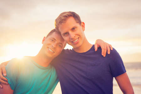 Gay couple on the beach at sunset 스톡 콘텐츠