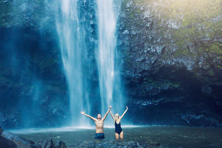 Couple enjoying pool at the base of large waterfall in Hawaii photo