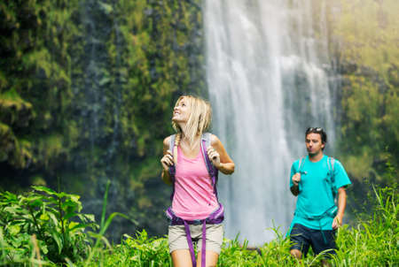 Couple having fun together outdoors on hike to amazing waterfall in Hawaii. photo