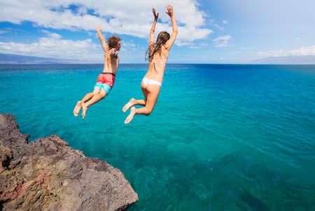 estilo de vida: Amigos de penhasco saltando no oceano, verão divertido estilo de vida. Imagens
