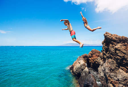 sky dive: Friends cliff jumping into the ocean, summer fun lifestyle.