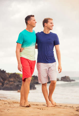 Young happy gay couple walking on the beach photo