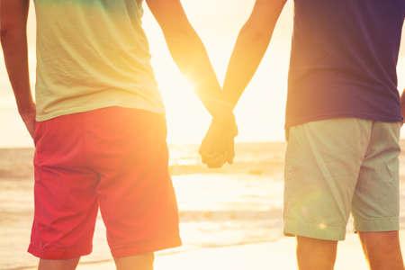 해변에서 석양을보고 손을 잡고 행복한 게이 커플 스톡 콘텐츠