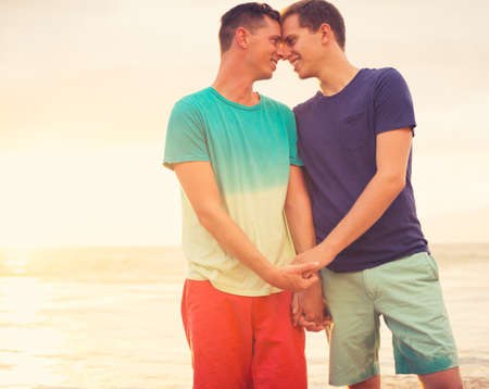 adult sex: Gay couple on the beach at sunset Stock Photo