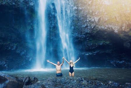 Couple enjoying pool at the base of large waterfall in Hawaii photo