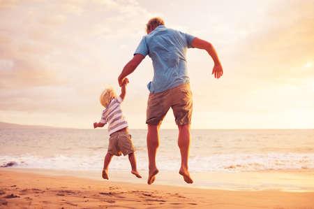 Vader en zoon springen van vreugde op het strand bij zonsondergang