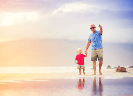 Happy father and son walking on the beach at sunset holding hands