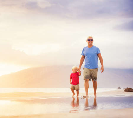 Happy father and son walking on the beach at sunset holding hands photo