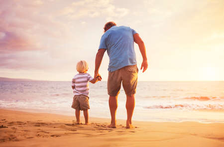Father and son standing on the sea shore holding hands at sunset Stockfoto