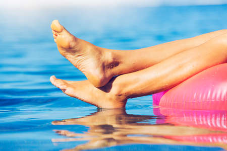 feet relaxing: Sexy young woman in bikini relaxing floating in the ocean, close up view of legs and feet