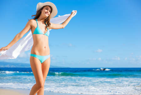 Beach vacation. Beautiful woman in sunhat and bikini enjoying perfect sunny day on the beach. photo