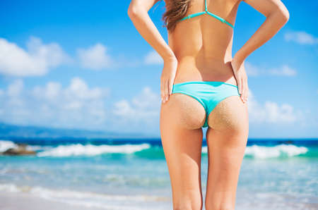 nude ass: Beautiful sexy young woman in small bikini with sandy butt on the beach
