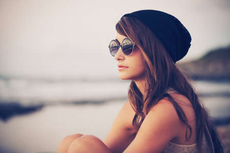 Fashion portrait of young hipster woman with hat and sunglasses on the beach at sunset, retro style color tones Foto de archivo