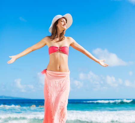 Beach vacation. Happy woman enjoying sunny day at the beach. Open arms, freedom, happiness and bliss.