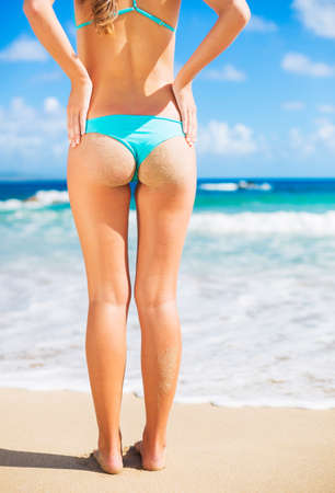 Sexy girl with perfect sandy butt at the beach photo