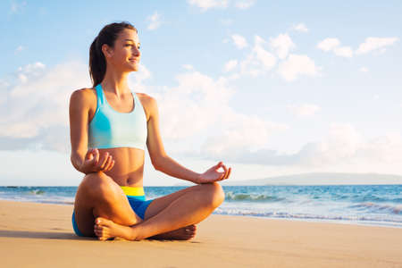 lotus pose: Young woman practicing yoga on the beach at sunset.