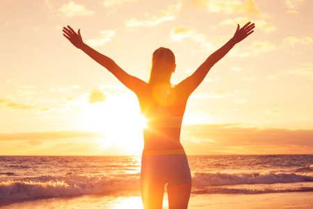 Zdarma šťastná žena otevřenou náručí při západu slunce