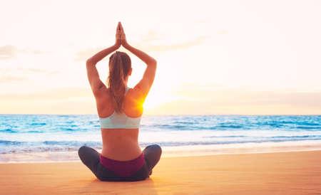 Vrouw beoefenen van yoga op het strand bij zonsondergang