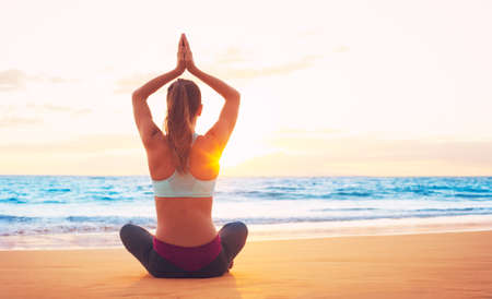 Woman practicing yoga on the beach at sunset photo