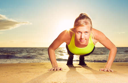 plank position: Fitness young woman doing push ups on beach at sunset. Outdoor workout.