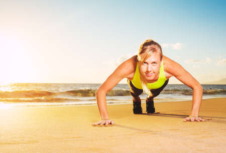 push: Fitness young woman doing push ups on beach at sunset. Outdoor workout.