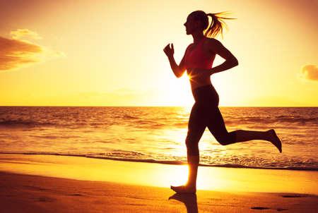 fitness: Mulher correndo na praia ao pôr do sol