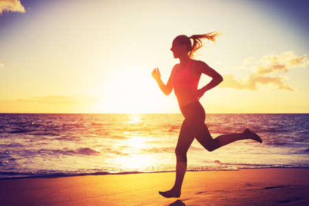 Vrouw die op het strand bij zonsondergang